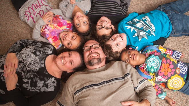 Portrait of Tim McFalls, bottom, with, clockwise from lower left corner, his wife Trudy, and their children, 10-year-old Morgan, 6-year-old Mileigh, 12-year-old Mason, 8-year-old Matthew, and 5-year-old Mickinley in their Stratford home. Mason is their biological child and the other children are adopted. Tim and Trudy neglected their own physical needs and saw their weight get out of control as they cared for their family . Last year, the couple underwent bariatric surgery about seven months apart. Tim has lost 125 pounds, and Trudy lost 40 pounds in the past four months. 01.16.15