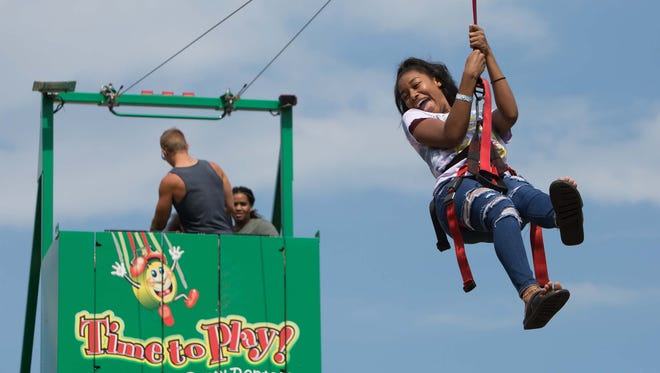 Lee'Ajiah Thomas-Gant of Flint rides a zip line during GM River Days on the Detroit riverfront in Detroit on June 23, 2018.