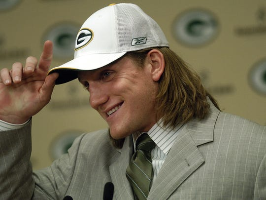 Green Bay Packers first-round draft choice A.J. Hawk gets ready to take his cap off to show off his long hair to the media inside Lambeau Field.