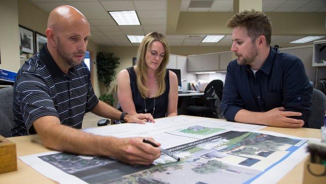 Ryan Trudell, senior landscape architect, left; Laura Thelen, landscape architect; and Matthew Thomas, landscape designer, work on some last-minute details on the design of the memorial.