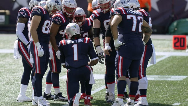 New England Patriots quarterback Cam Newton (1) calls signals in the huddle in the first half of an NFL football game against the Miami Dolphins, Sunday, Sept. 13, 2020, in Foxborough, Mass.