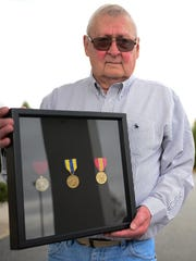 "William ""Gus"" Gustafson holds his metals that he has received 50 years after his service  during the Cold War. Tuesday, Dec. 5, 2017."
