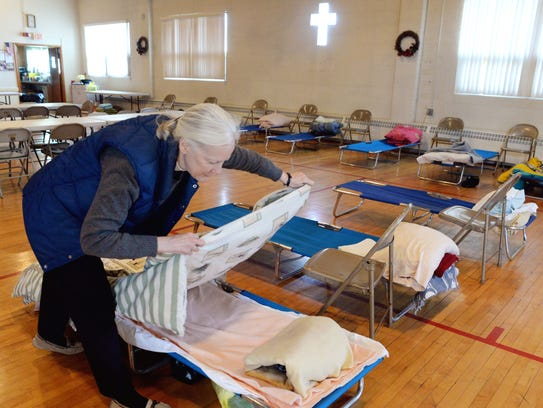 Rev. Ellen Rutherford makes up cots inside her church