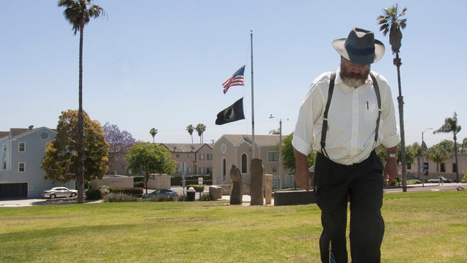Steve Schleder places an American flag on the grave of James Sumner in Cemetery Memorial Park (formerly known as St. Mary's Cemetery) in Ventura. Schleder spent Saturday placing flags on both marked and unmarked graves in the park for Monday's Memorial Day service. This year, Confederate veteran John Gaynor will be recognized during the ceremony.