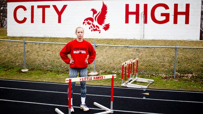 City High standout track athlete Sarah Plock takes a break from warm ups for a photo on Thursday, April 3, 2014. Benjamin Roberts / Iowa City Press-Citizen