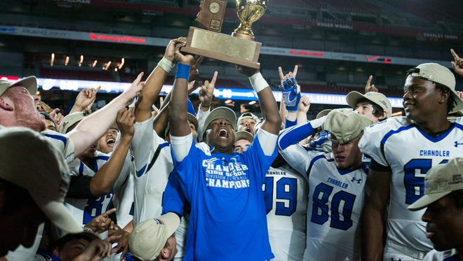 The Chandler Wolves hold up the Division I state championship trophy after winning against the Hamilton Huskies on Nov. 28, 2014, at the University of Phoenix Stadium.