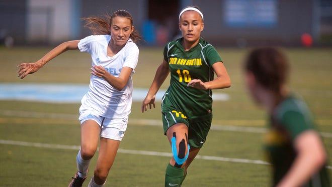 Burr and Burton midfielder Hannah Pinkus, center, dribbles past a South Burlington defender during Wednesday's girls soccer game in South Burlington.