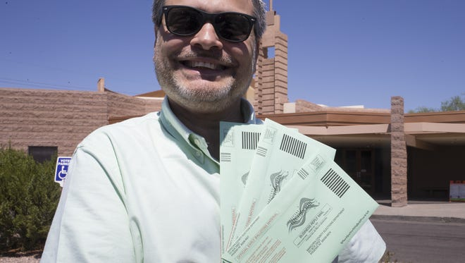 """Louis Hoffman shows the three ballots he collected to drop off at the polls at the North Scottsdale United Methodist Church on Aug. 30, 2016. He was seeing whether poll workers or Republican poll observers would enforce a new state ban on so-called """"ballot harvesting."""""""