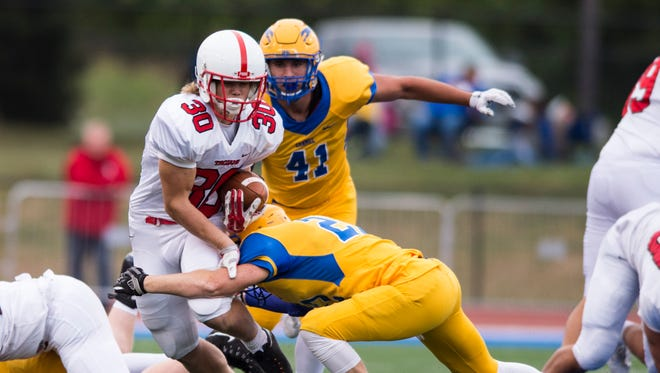 Center Grove High School freshman Carson Steele (30) gets hit by a Carmel defender as he rushes the ball out of the backfield during the first half of an IHSAA high school football game at Carmel High School, Friday, September 1, 2017.