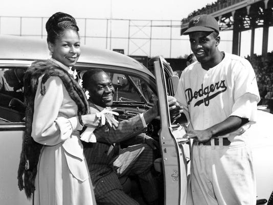 FILE - In this Sept. 23, 1947, file photo, Brooklyn Dodgers baseball player Jackie Robinson, right, receives the keys to a car from tap dancer Bill Bojangles Robinson as Jackie Robinson's wife, Rachel, looks on at Ebbets Field in New York. The car was presented to Robinson in celebration of the team winning the National League championship.  A rare jersey from Jackie Robinson's historic rookie season with the Brooklyn Dodgers 70 years ago could be available for someone with a few spare millions. The jersey, part of a Heroes of Sports offering by Heritage Auctions, has been certified by Mears, one of the top memorabilia authentication companies. It is accompanied by a letter from Robinson's widow, Rachel, saying it is the one brought home by the Hall of Famer at the end of the 1947 season, when he became the first black player in the majors and earned Rookie of the Year honors. (AP Photo/Harry Harris, File)
