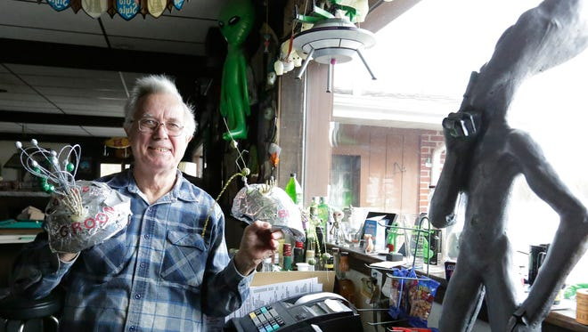 Bill Benson, holding groom-and-bride alien hats worn at weddings, calls Long Lake the UFO capital of the world. He operates on the lake's shore Benson's Hide-A-Way, full of UFO and extraterrestrial memorabilia.