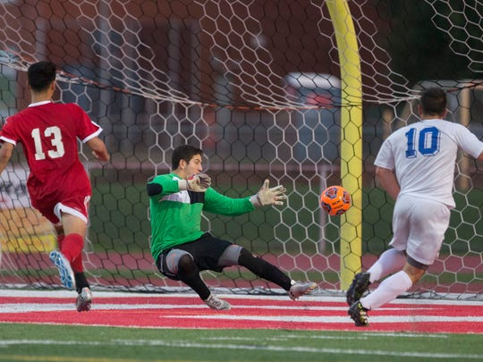 Holmdel's Anthony Arena puts in one of  his five goal as Ocean goalie Max Winters tries to react to his shot. Holmdel Boys Soccer easily defeats Ocean in SCT Conference Final in Ocean Township on October 26, 2017.