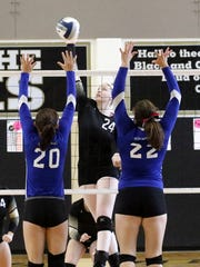 Sophia Sariego of Corning goes up for the kill as Horseheads' Beth Collins (20) and Cassidy Wilcox (22) try for the block during the Section  4 Class AA final at Corning-Painted Post High School on Nov. 5.