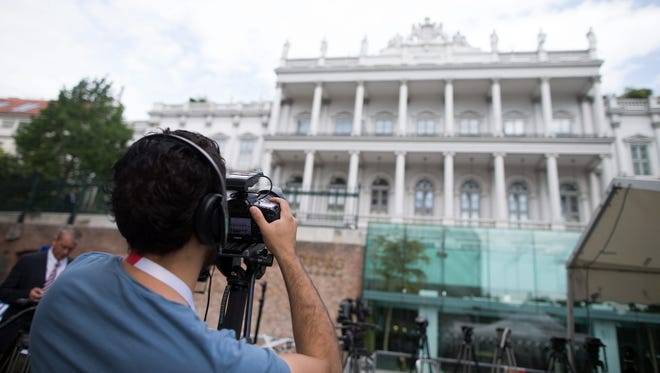 A journalist takes pictures in front of the Palais Coburg in Vienna where talks between world powers and iran continue on July 8, 2015.