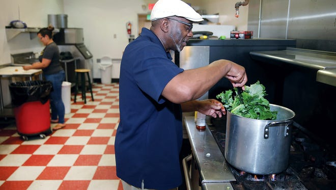 David Stewart of New Day Ministry makes a meal to be served to homeless diners at Evergreen Kitchen in Bremerton. Laughing Dog Kitchen rents space in the kitchen each week and donated some of its time to New Day to cook meals each week.