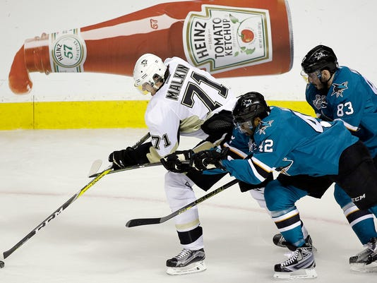 Pittsburgh Penguins' Evgeni Malkin, left, moves the puck past San Jose Sharks' Joel Ward (42) and Matt Nieto (83) during the first period of Game 4 of the NHL hockey Stanley Cup Finals on Monday, June 6, 2016, in San Jose, Calif. (AP Photo/Eric Risberg)