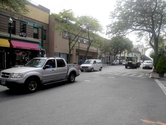 Cars drive along Main Street in New Rochelle Sept. 19. Main and Huguenot streets have each been one-way streets in different directions since 1961. The city is considering converting both to two-way streets.