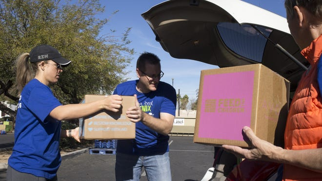 Volunteers Bryan Jacewicz (right) and Alicia Bustillo (left) load a vehicle on Dec. 9, 2016, at St. Pilgrim Rest Baptist Church in Phoenix.