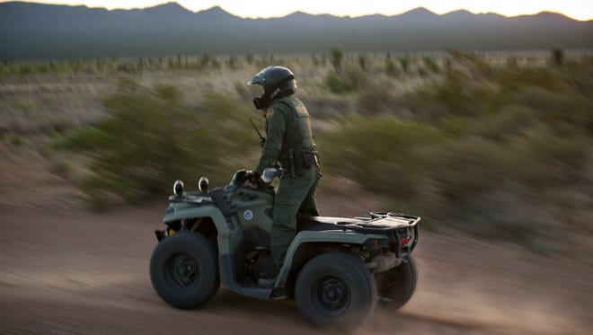 A Border Patrol agent on an ATV looks for footprints or other signs of human disturbance along Highway 81, south of Hachita, New Mexico.