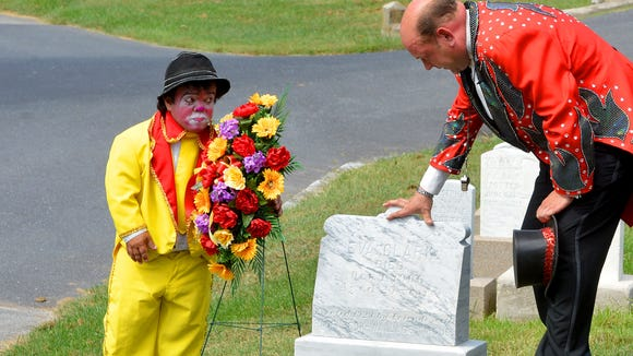 Cole Brothers Circus performer Marvin of Mexico stands next to the wreath he just placed as ringmaster Chris Connors touches the headstone of Eva Clark, a young aerialist circus performer killed in 1906. The circus held a small ceremony at Clark's gravesite in Thornrose Cemetery as they remember her in Staunton on Tuesday, Sept. 2, 2014.
