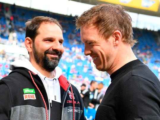 FILE - In this March 31, 2018 file photo Cologne's coach Stefan Ruthenbeck, left, and Hoffenheim's coach Julian Nagelsmann arrive for the German Bundesliga soccer match between TSG 1899 Hoffenheim and 1. FC Cologne in Sinsheim, Germany.  Cologne will part ways with Stefan Ruthenbeck at the end of the season regardless of whether his side clinches Bundesliga survival or not. (Uwe Anspach/dpa via AP,file)