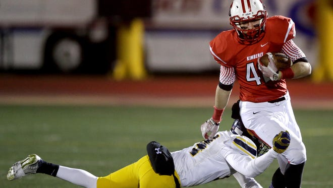 Marquette University High School's Kalman Daughtery tries to tackle Kimberly High School's Keegan Downham on Nov. 13 at Titan Stadium in Oshkosh. The Papermakers rolled to a 49-20 state semifinal win and will play for their third consecutive WIAA state title on Friday.