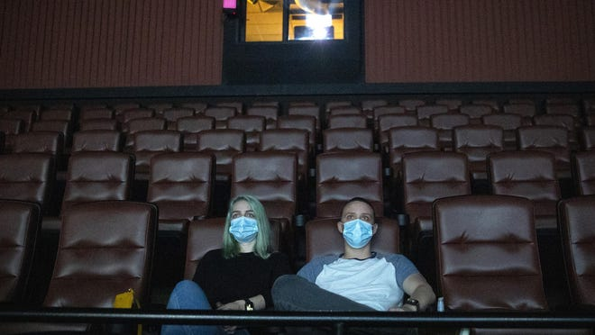 """Kayleigh Tansey and Justin Smith, of Kyle, watch the movie """"The Invisible Man"""" at EVO Entertainment on May 4. The movie theater in Kyle reopened after Gov. Greg Abbott lifted the shelter in place order and allowed retail stores, restaurants and some other businesses to open to the public at no more than 25% capacity."""