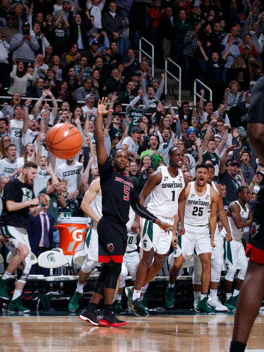 Michigan State's Joshua Langford (1) celebrates his 3-pointer in overtime along with fans and players on the bench Kenny Goins (25) and Ben Carter, left, as Rutgers' MIke Williams (5) reacts during overtime of an NCAA college basketball game, Wednesday, Jan. 10, 2018, in East Lansing, Mich. Michigan State won 76-72 in overtime. (AP Photo/Al Goldis)