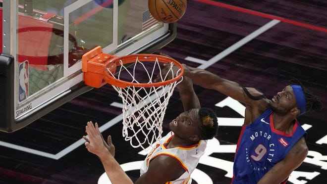 Atlanta Hawks center Clint Capela (15) and Detroit Pistons forward Jerami Grant (9) look for a rebound during the first half of an NBA basketball game Wednesday, Jan. 20, 2021, in Atlanta.