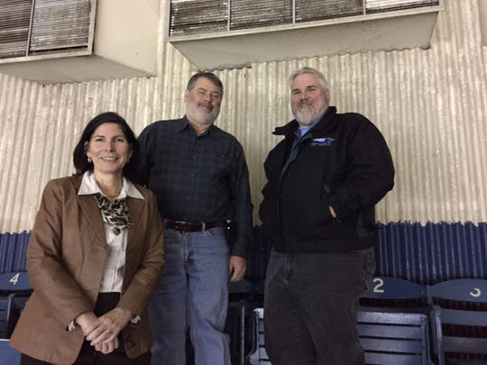 Hara Arena officials (left to right) Karen Wampler, Rue Wampler and Pat Siehl stand next to Crosley Field seats.