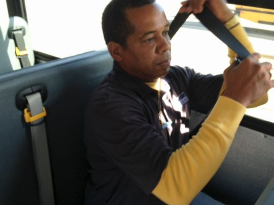 Des Moines school bus driver Daniel Johnson demonstrates how students will put on a seat belt while riding to school.