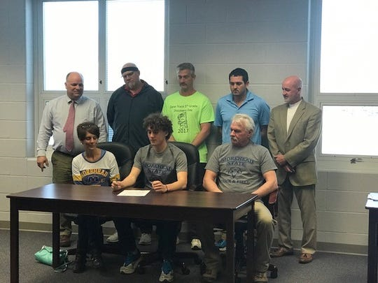 Cole Clever, seated middle, is flanked by his parents as he signs his letter of intent to run track and cross country at Morehead State, beginning in the fall of 2018. School officials and coaches are in the back row.