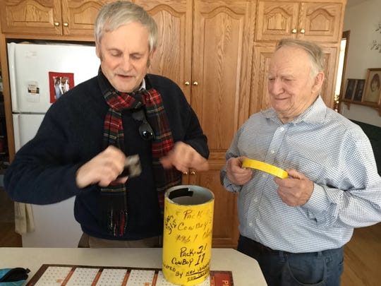 "P.J. Vidani, left, delivers a piece of goal post to Leland Baenen, who worked at the famed ""Ice Bowl"" game in 1967 as an auxiliary policeman. Vidani believes the piece was part of a larger section that was carried out of Lambeau Field after the game and cut into pieces."