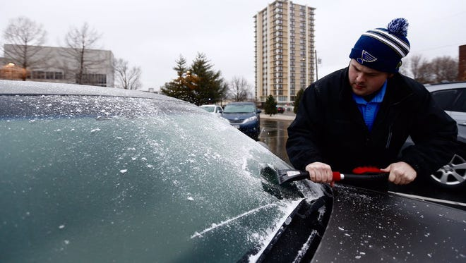 MSU student Zachary Dobbs scrapes ice off his windshield on Saturday.