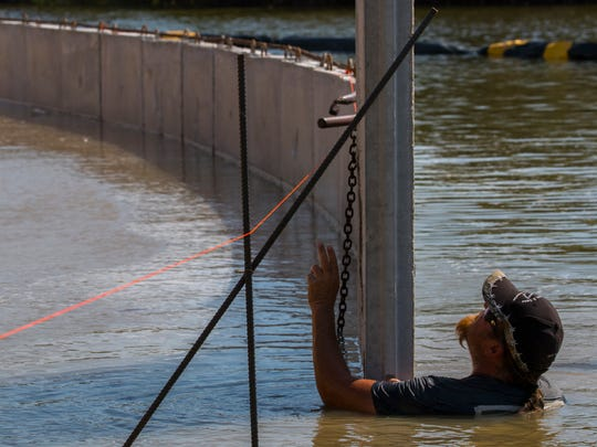 Bubba Williamson, of Williamson & Sons Marine Construction, centers a concrete panel during the assembly process of a seawall for a new Cape Coral home Monday afternoon, 9/18/17.