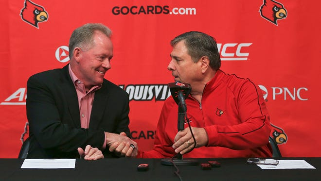 Louisville football coach Bobby Petrino shakes the hand of athletic director Tom Jurich after the public announcement of Petrino's seven-year, $30.65 million contract extension Thursday.