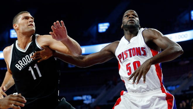 The Nets' Brook Lopez and the Pistons' Joel Anthony look for a rebound.