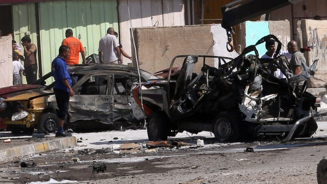 Citizens inspect the site of a car bomb attack in Baghdad on Sept. 30.