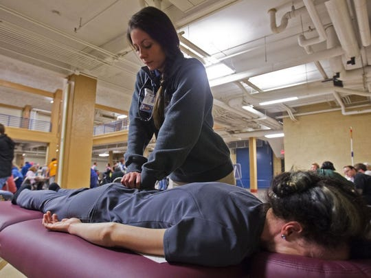 Rhyan Bingham, a medical student at Lincoln Memorial University College of Otheopathic Medicine, works on a patient during a Remote Area Medical event at Chilhowee Park Saturday, Feb. 6, 2016.  (WADE PAYNE/SPECIAL TO THE NEWS SENTINEL)