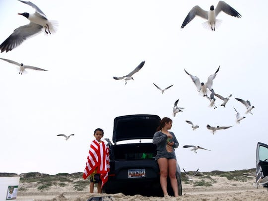 CALLER-TIMES FILE Jon Marquez, 9, (right) and McCoy Gonzales eat snacks as sea gulls fly nearby during spring break 2015 at JP Luby Surf Park.