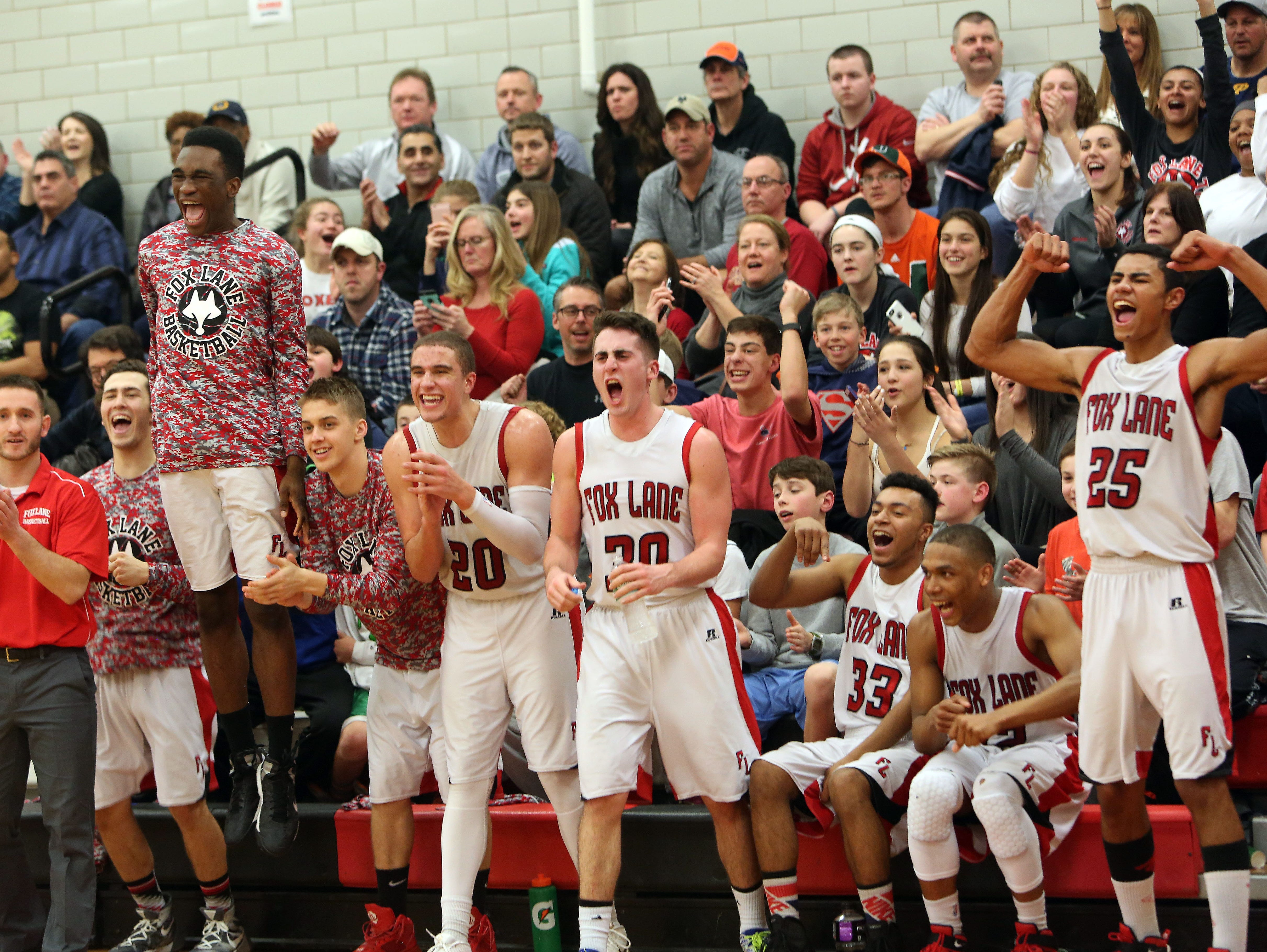Fox Lane players celebrate their 78-45 victory over New Rochelle in the Class AA quarterfinals at Fox Lane High School in Bedford Feb. 20, 2016.