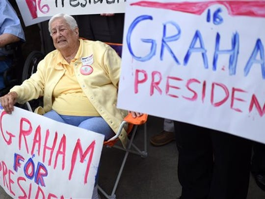 Mary Bauld of Clemson, S.C. holds a sign supporting Sen. Lindsey Graham, R-S.C. before his announcement for the presidency, Monday, June 1, 2015, in Central, S.C.