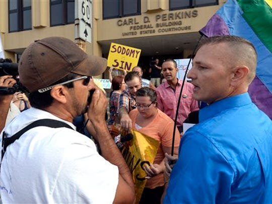 Edgar Orea, left, and Dwayne D. Beebe-Franqui argue on the steps of the Carl D. Perkins Federal Building in Ashland, Ky., Thursday, Sept. 3, 2015. Orea, a supporter of Rowan County Clerk Kim Davis, and Beebe-Franqui a supporter of same sex marriage were waiting for the arrival of Kim Davis in Federal Court. Davis and her deputy clerks have been summoned to a hearing Thursday before Judge David Bunning. Davis stopped issuing licenses to all couples in June after the U.S. Supreme Court legalized gay marriage.