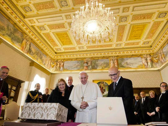 Pope Francis exchanges gifts with President of Malta, Marie Louise Coleiro Preca, left, and her husband Edgar, right, during a private audience at the Vatican, Saturday, Dec. 17, 2016.