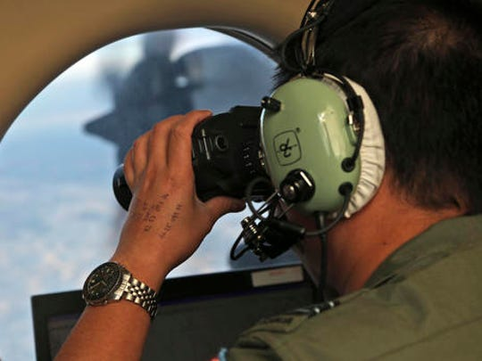 FILE - In this March 22, 2014, file photo, Flight Officer Jack Chen uses binoculars at an observers window on a Royal Australian Air Force P-3 Orion during the search for missing Malaysia Airlines Flight MH370 in Southern Indian Ocean, Australia. The Joint Agency Coordination Center in Australia said Tuesday, Jan. 17, 2017 that the search for Malaysia Airlines Flight 370 had officially been suspended after crews finished their fruitless sweep of the 120,000-square kilometer (46,000-square mile) search zone west of Australia.