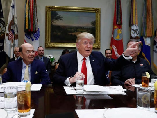 President Donald Trump, flanked by Commerce Secretary-designate Wilbur Ross, left, and Harley Davidson President and CEO Matt Levatich talks to media before a lunch meeting with Harley Davidson executives and union representatives in the Roosevelt Room of the White House in Washington, Thursday, Feb. 2, 2017. (AP Photo/Carolyn Kaster)