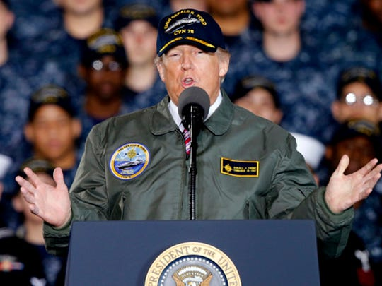 FILE - In this March 2, 2017, photo, President Donald Trump gestures as he speaks to Navy and shipyard personnel aboard nuclear aircraft carrier Gerald R. Ford at Newport News Shipbuilding in Newport News, Va. The ongoing stories of ties between President Donald Trump and Russian officials have challenged, amused, angered and inspired spy novelists. The Cold War ended decades ago, but writers now see a new wave of possible plot twists and plots to avoid.