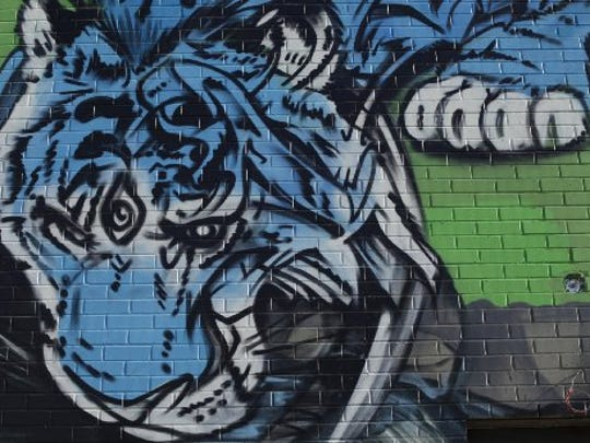"""Detail shot of a mural being painted by the artist Kobie Solomon on the outside wall of HopCat Detroit that is scheduled to open its doors in December. Solomon is well-know for his 10-story """"Chimera mural"""" on Detroit's Russell Industrial Center."""