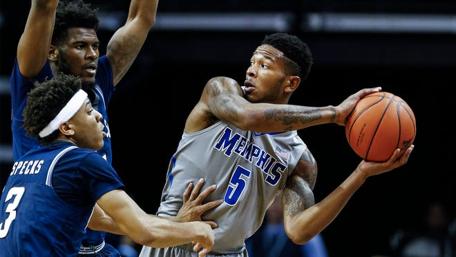 University of Memphis guard Markel Crawford (right) looks to pass around the Jackson State University defense during second half action at the FedExForum.
