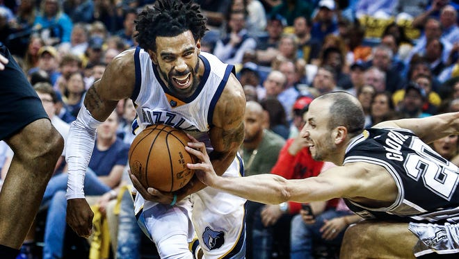 Memphis Grizzlies guard Mike Conley (left) drives the lane against the San Antonio Spurs defender Manu Ginobili (right) during second quarter action in the sixth game of their NBA first round playoff series at the FedExForum on April 27, 2017.